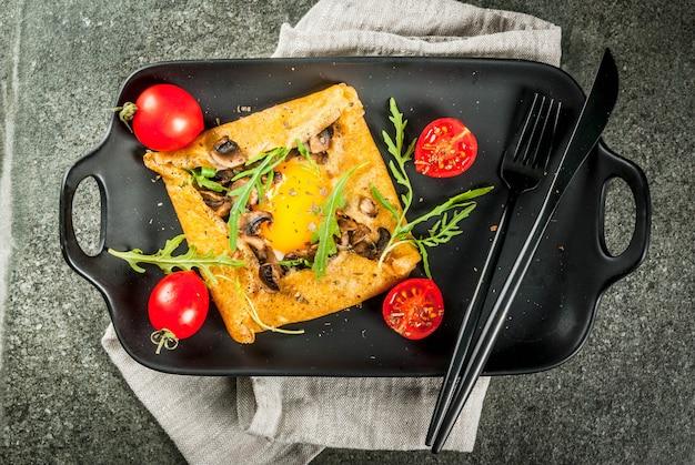 Franse keuken ontbijt lunch snacks veganistisch eten traditioneel gerecht galette sarrasin pannenkoeken met eieren kaas gebakken champignons rucola bladeren en tomaten op zwarte stenen tafel Premium Foto