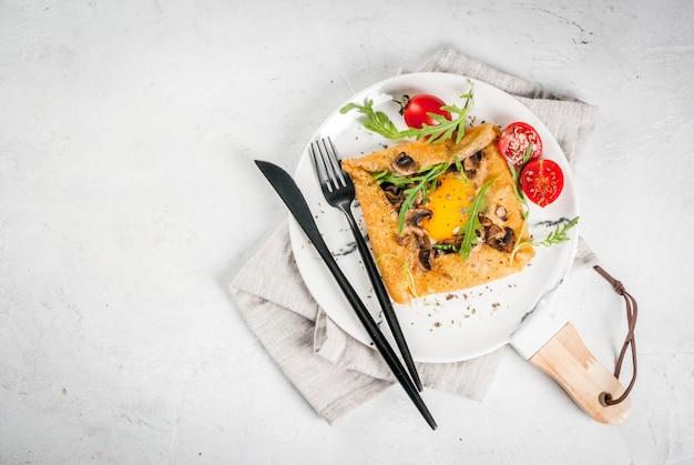 Franse keuken ontbijt lunch snacks veganistisch eten traditioneel gerecht galette sarrasin pannenkoeken met eieren kaas gebakken champignons rucola bladeren en tomaten Premium Foto