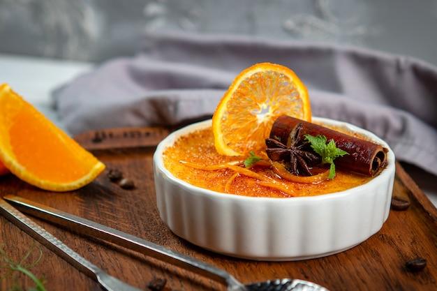 Franse vanille creme brulee dessert in keramische kom op houten bord Premium Foto