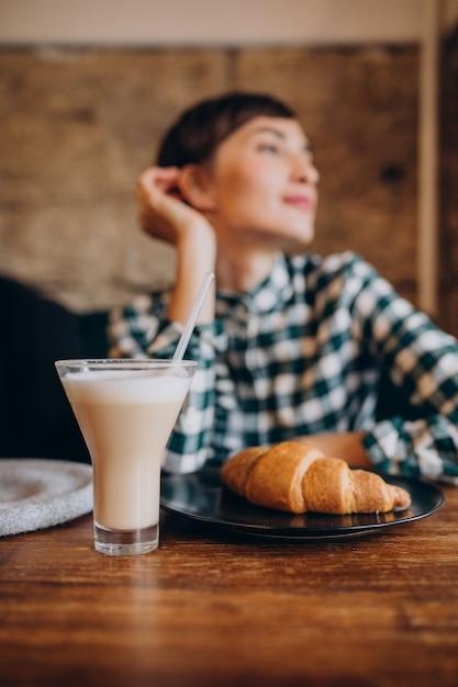 Franse vrouw in café latte drinken en croissant eten Gratis Foto