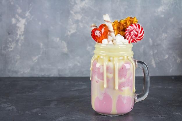 Freakshake van roze smoothie, room. monstershake met lolly's, wafels en marshmallow. Premium Foto