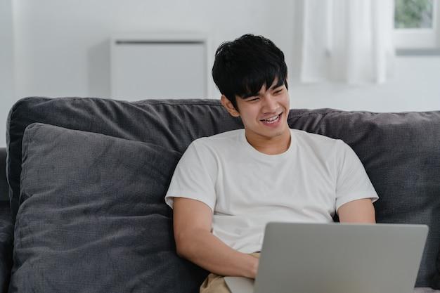 Freelance aziatische man aan het werk thuis, mannelijke creatief op laptop op sofa in de woonkamer. de ondernemer van de bedrijfs jonge menseneigenaar, speelt computer, die sociale media op werkplaats controleren bij modern huis. Gratis Foto