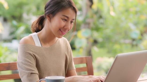 Freelance aziatische vrouw die thuis, bedrijfswijfje werkt dat aan laptop zitting op lijst in de tuin in ochtend werkt. lifestyle vrouwen werken thuis concept. Gratis Foto
