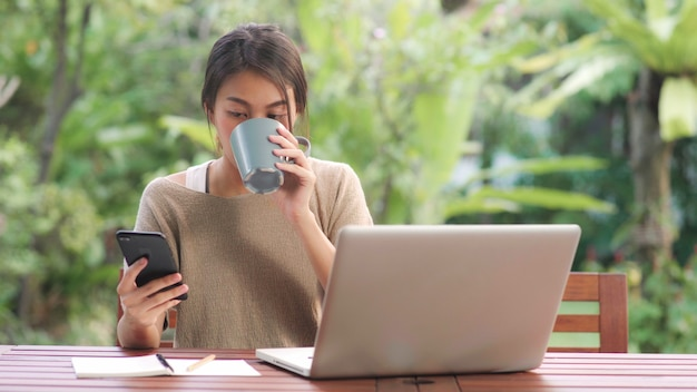 Freelance aziatische vrouw thuis werken, zakelijke vrouw die op laptop werkt en het gebruik van mobiele telefoon drinken koffie zittend op tafel in de tuin in de ochtend. Gratis Foto