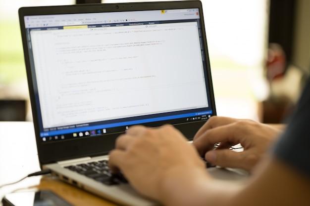 Freelance programmeur of ontwikkelaar die thuis werkt en broncode intypt met laptop Premium Foto