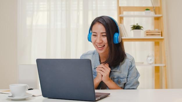 Freelance zakelijke vrouwen vrijetijdskleding met behulp van laptop werkgesprek videoconferentie met klant op de werkplek in de woonkamer thuis. het gelukkige jonge aziatische meisje ontspant het zitten op bureau doet werk in internet. Gratis Foto
