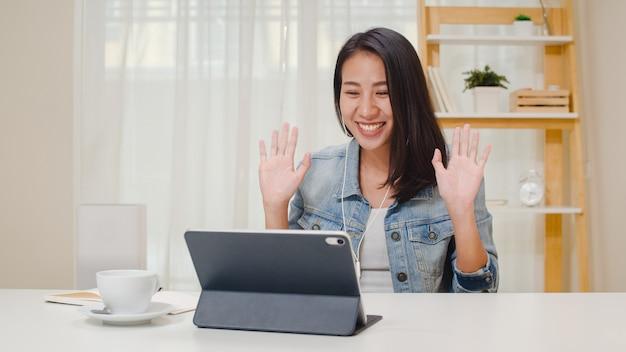 Freelance zakelijke vrouwen vrijetijdskleding met behulp van tablet werkgesprek videoconferentie met klant op de werkplek in de woonkamer thuis. het gelukkige jonge aziatische meisje ontspant het zitten op bureau doet werk in internet. Gratis Foto