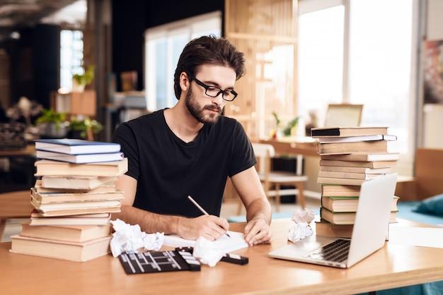 Freelancer bebaarde man notities zitten aan de balie. Premium Foto