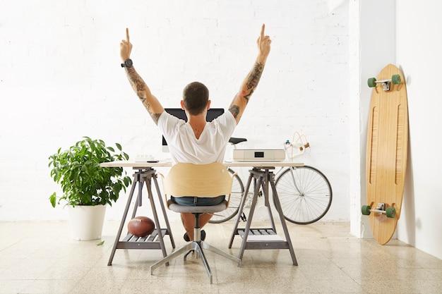 Freelancer op zijn bureaublad met personal computer, omringd door zijn hobbyspeelgoed in lichte kamer voor witte bakstenen muur, strekt zijn armen uit en toont ongecensureerd gebaar Gratis Foto