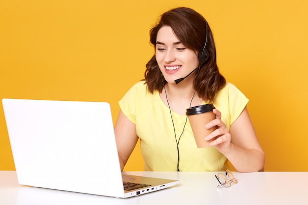 Freing freelance operator die online werkt met headsets en laptopcomputer op kantoor of thuis. vrolijke callcenter vrouw praten met klant en koffie drinken, beind in goed humeur. Premium Foto
