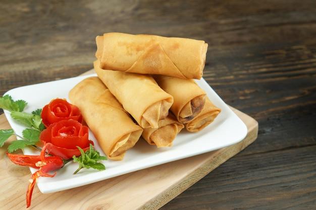 Fried chinese-de lentebroodjes dienden met spaanse pepersaus en verfraaide roze tomaten met groen leaved op hout, ruimte. concept aziatisch eten Premium Foto