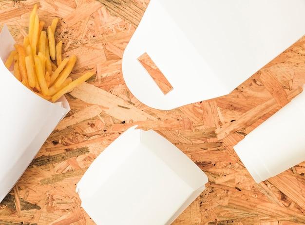 Frieten en wit pakketmodel op houten achtergrond Gratis Foto