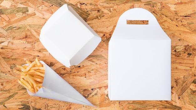 Frieten in document kegel en wit pakket op houten achtergrond Gratis Foto