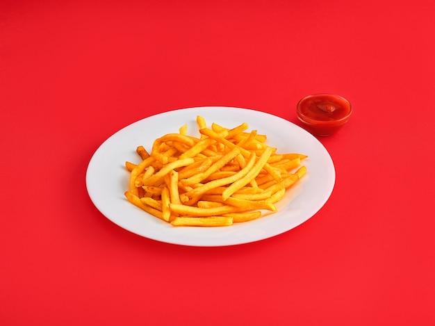 Frieten op een plaat op rood Gratis Foto
