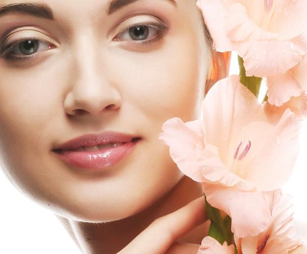 Fris gezicht met gladiolenbloemen in haar handen Premium Foto