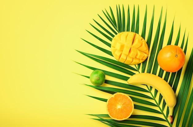 Fris oranje, banaan, ananas, mango smoothie en sappige vruchten op palmbladeren op gele achtergrond. detox zomerdrankje. vegetarisch concept. Premium Foto