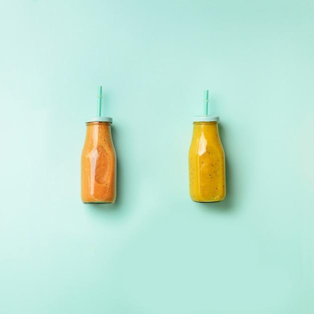 Fris oranje, banaan, ananas, mango smoothies en sappige vruchten op blauwe achtergrond. detox zomerdrankje. vegetarisch concept. Premium Foto