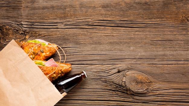Frisdrank en broodjes in een papieren zak Gratis Foto