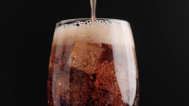 Frisdrank met ijs op een zwarte close-up als achtergrond Premium Foto