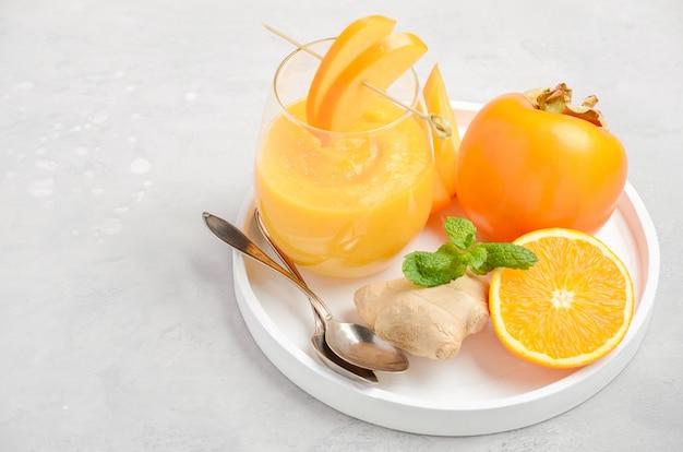Frisse gezonde smoothie met persimmon, sinaasappel en gember. Premium Foto