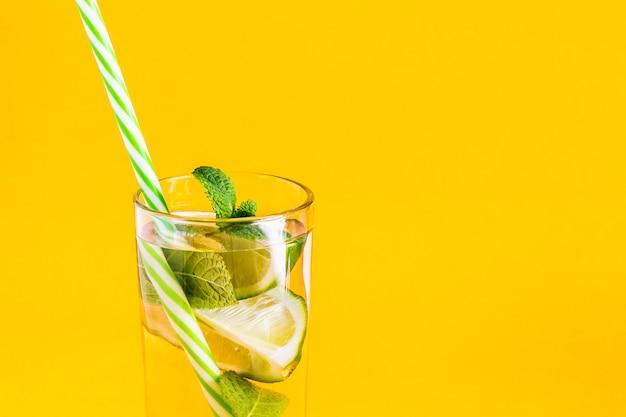 Frisse zomerlimonade met water, limoen en munt met een rietje Premium Foto