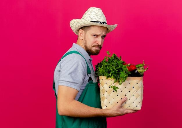 Fronsen jonge knappe slavische tuinman in uniform en hoed staande in profiel te bekijken op zoek mand met groenten Gratis Foto