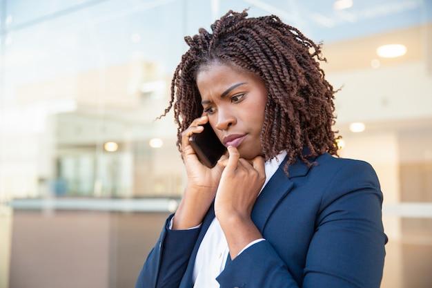 Fronsende betrokken manager die op mobiel spreekt Gratis Foto