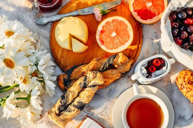 Fruit, croissants, thee en bloemen op tafellaken in de zomerzon. picnic-concept Premium Foto