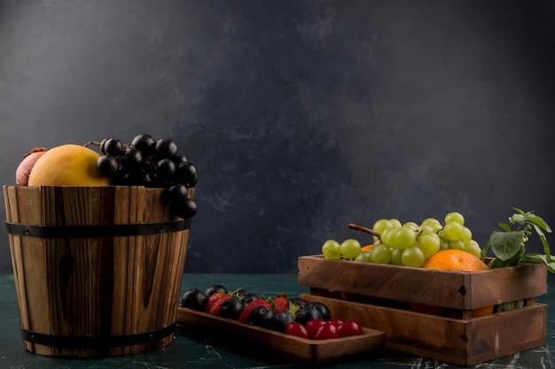 Fruit en bessenmix in houten containers op blauwe ruimte Gratis Foto