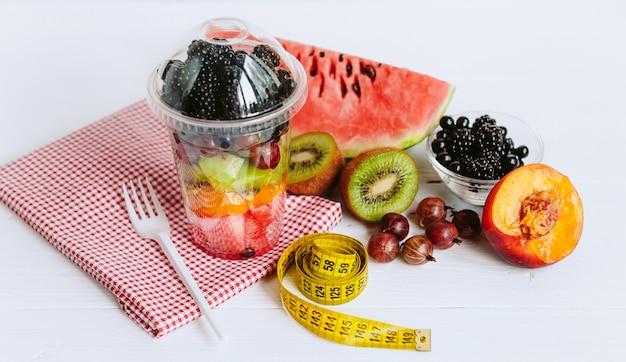 Fruit in een glas en een meetlint voor het meten van het lichaam Premium Foto