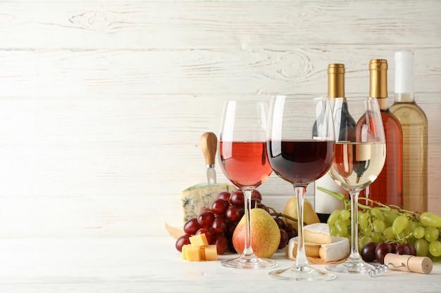 Fruit, kaas, flessen en glazen met verschillende wijn op wit Premium Foto