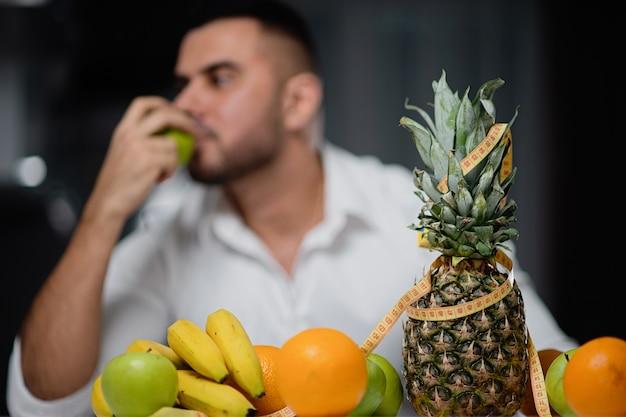 Fruit op de lijstclose-up met een man op de achtergrond. het concept van een gezonde levensstijl Premium Foto