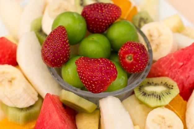 Fruit op een bord. groene pruim, aardbei, banaan, kiwi, watermeloen, sinaasappel en appel. Premium Foto