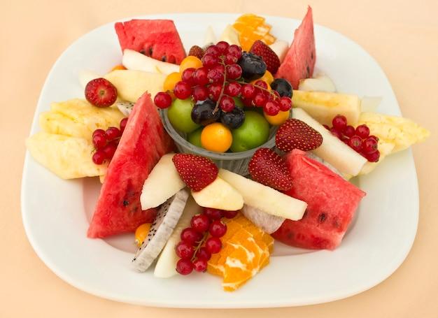 Fruit op een bord. groene pruim, rode bes, bosbes, aardbei, physalis, pitahaya Premium Foto