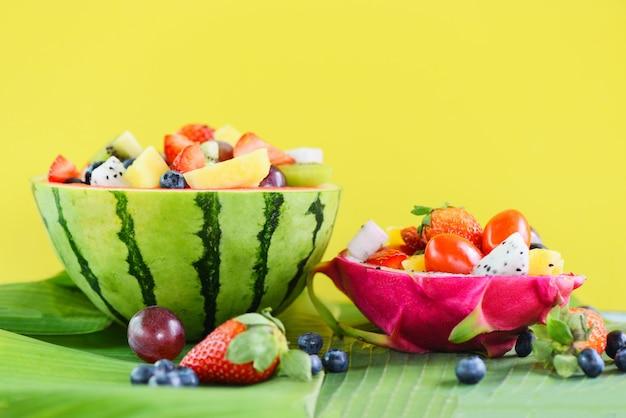 Fruit slakom geserveerd in dragon fruit en watermeloen groenten gezonde voeding aardbeien oranje kiwi bosbessen druif ananas tomaat citroen verse zomer fruit tropisch op bananenblad Premium Foto