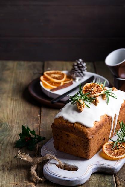 Fruitcake bestrooid met suikerglazuur, noten en droge sinaasappel op oude houten. kerst- en wintervakantie zelfgemaakte cake Premium Foto