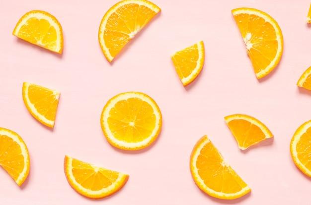 Fruitpatroon van verse stukjes sinaasappel op pastel achtergrond. bovenaanzicht. Premium Foto