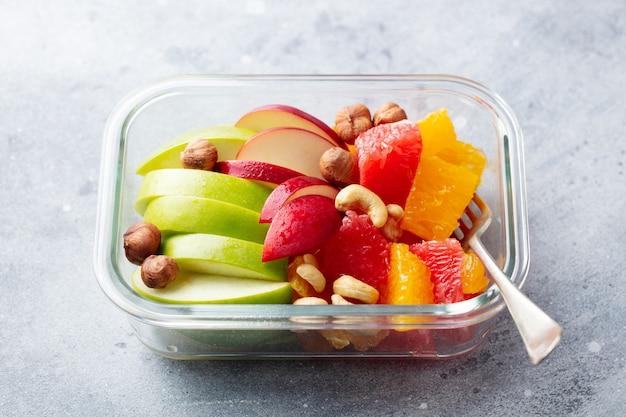 Fruitsalade en noten in een glazen container. gezond eten. Premium Foto