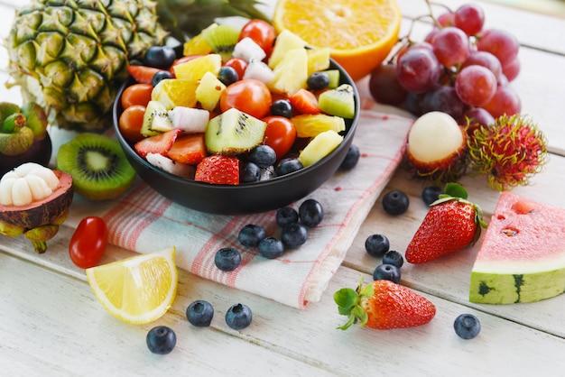 Fruitsalade kom verse zomer fruit en groenten gezonde biologische voeding watermeloen aardbeien sinaasappel kiwi bosbessen dragon fruit tropische druif tomaat citroen rambutan ananas Premium Foto