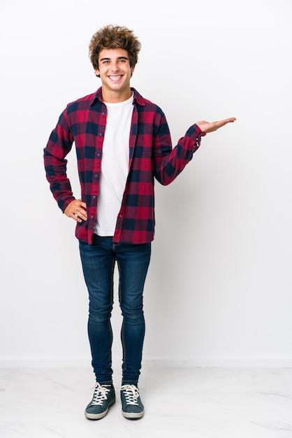 Full body jonge blanke man geïsoleerd met een kopie ruimte op een palm en met een andere hand op de taille. Premium Foto