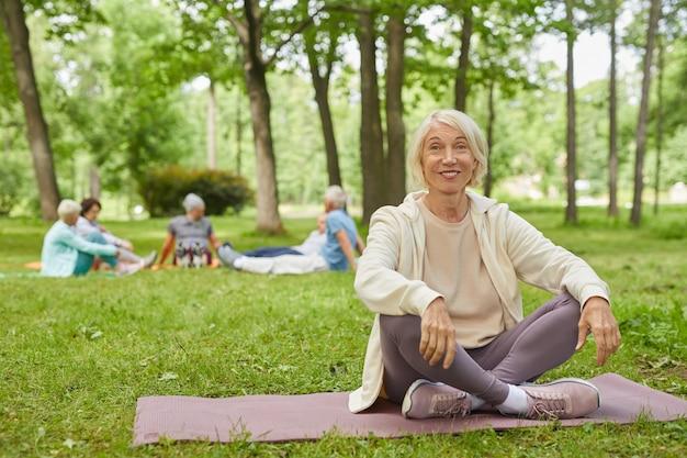 Full body shot van gelukkige senior vrouw met grijze haren zittend op de mat in park met gekruiste benen glimlachend in de camera Premium Foto