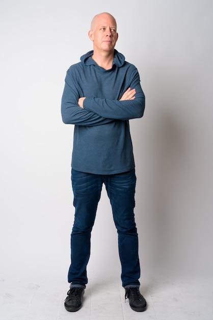 Full body shot van volwassen knappe kale man denken met gekruiste armen Premium Foto
