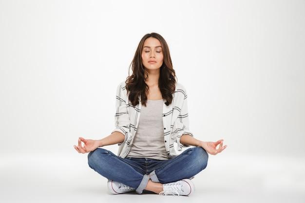 Full-length foto van geconcentreerde vrouw in vrijetijdskleding mediteren met gesloten ogen zittend in lotus houding op de vloer, geïsoleerd over witte muur Gratis Foto