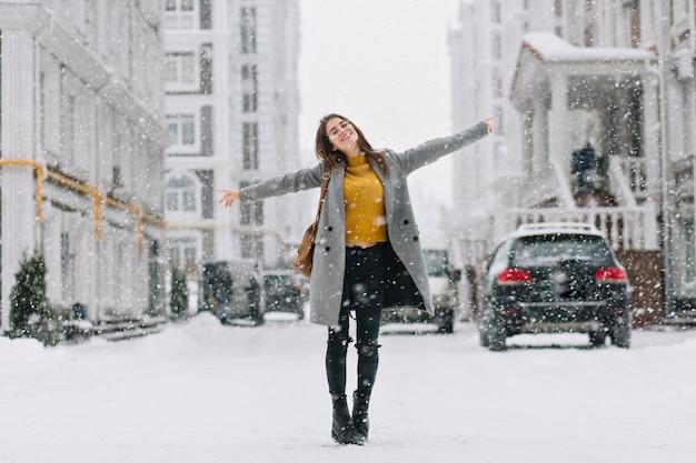 Full-length portret van romantische europese dame draagt een lange jas in een besneeuwde dag. buiten foto van geïnspireerde brunette vrouw genieten van vrije tijd in winter stad. Gratis Foto