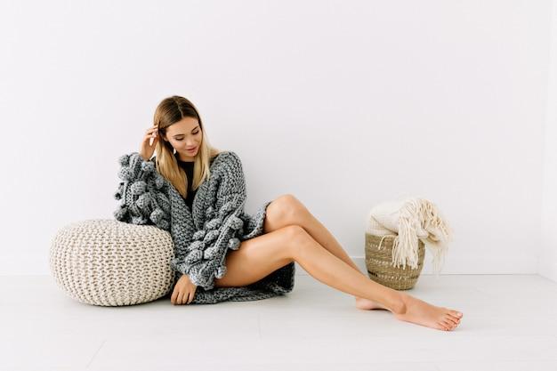 Full-length shot van aantrekkelijk vrouwelijk model met blond haar en mooie blote benen dragen gebreide trui poseren op geïsoleerde witte muur met zacht glimlach Gratis Foto