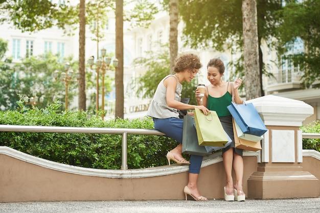Full-length shot van twee meisjes die pronken met hun aankopen in hun boodschappentassen Gratis Foto