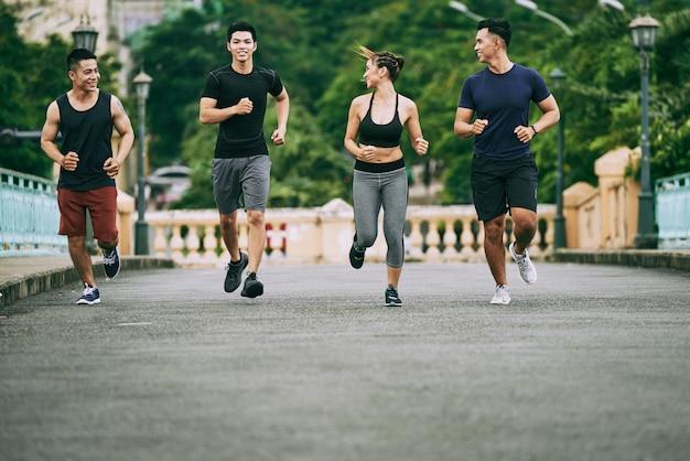 Full-length shot van vier mensen joggen in de ochtend Gratis Foto