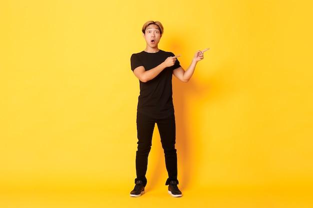 Full-length van verbaasd en onder de indruk aantrekkelijke aziatische man wijzende vingers rechter bovenhoek, logo, gele muur. Gratis Foto