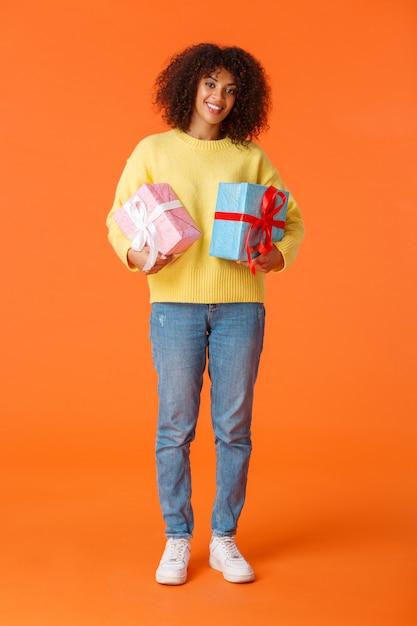 Full-length verticaal schot aantrekkelijke vrolijke afro-amerikaanse vrouw voorbereid op vakantie, kocht cadeautjes voor familie, glimlachend vrolijk met twee dozen geschenken, staande oranje Premium Foto