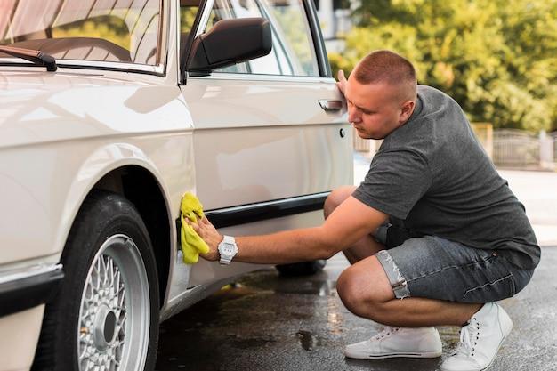 Full shot man auto met een doek schoonmaken Premium Foto